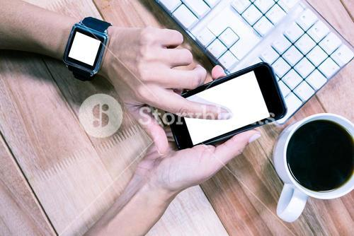 Feminine hands with smartwatch using smartphone