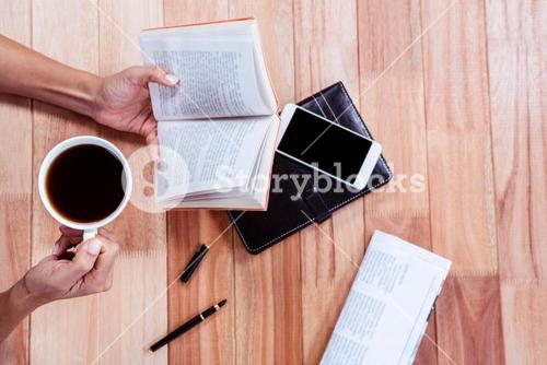 Overhead of feminine hands holding a book and coffee