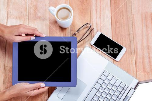 Overhead of feminine hands holding tablet