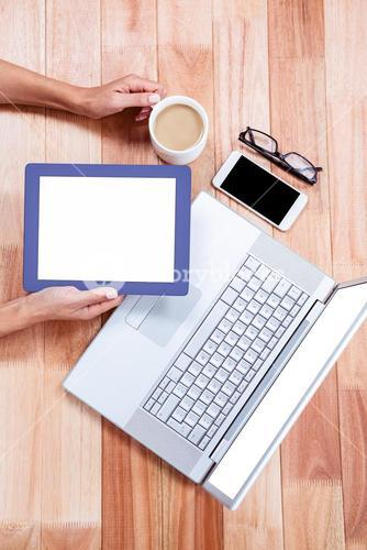 Overhead of feminine hands holding tablet and coffee
