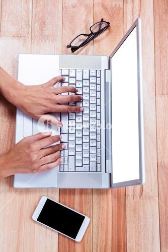 Overhead of female hands typing on laptop