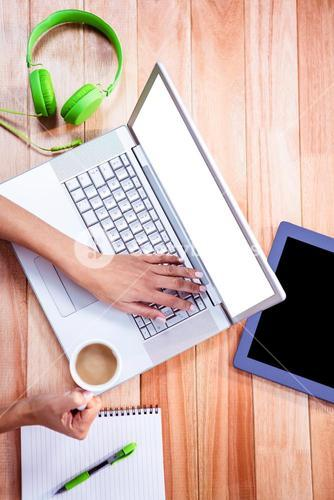 Overhead of feminine hands using laptop and holding coffee