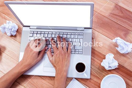 Part of hands typing on laptop