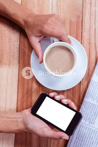 Part of hands holding smartphone and coffee