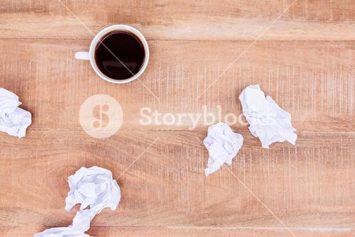Above view of coffee and paper ball