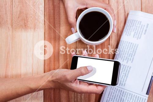 Part of hands holding coffee and smartphone