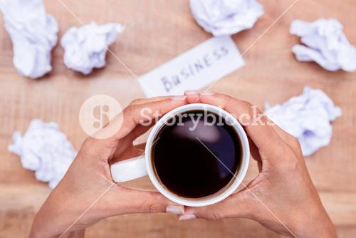 Businesswoman holding black coffee cup