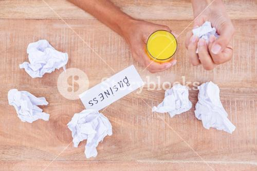 Businesswoman having orange juice and holding crumpled paper