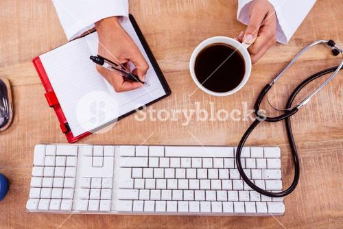 Doctor holding coffee cup and writing on diary