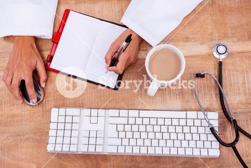 Doctor using mouse and writing on diary
