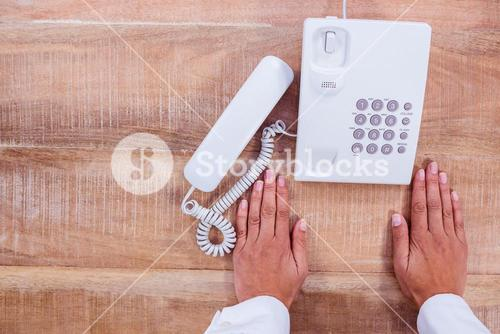 Businesswoman holding a phone at her desk