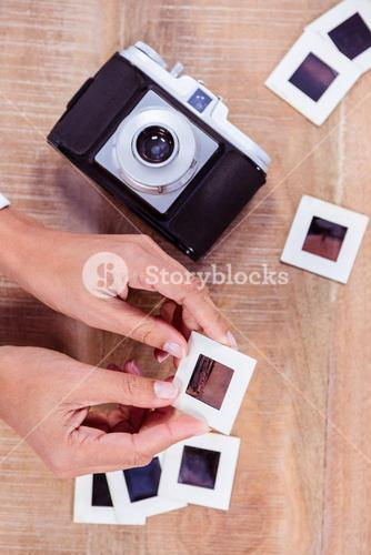 View of hands holding photo slides