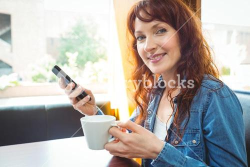 Mature student using phone in cafe