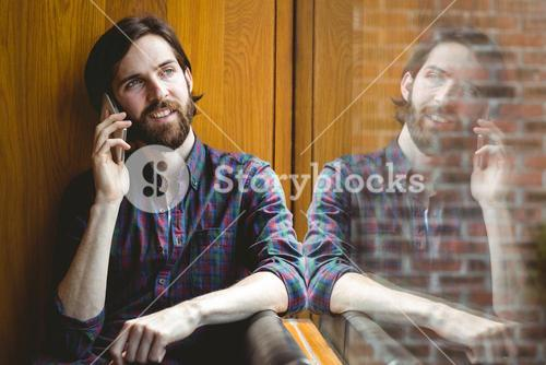 Hipster student on a call in canteen