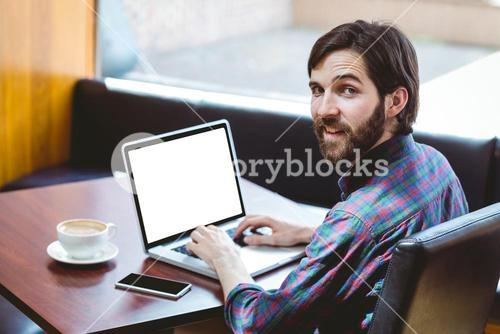 Hipster student using laptop in canteen