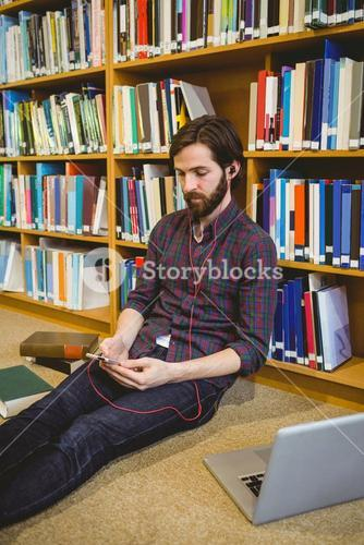 Student using phone in library on floor