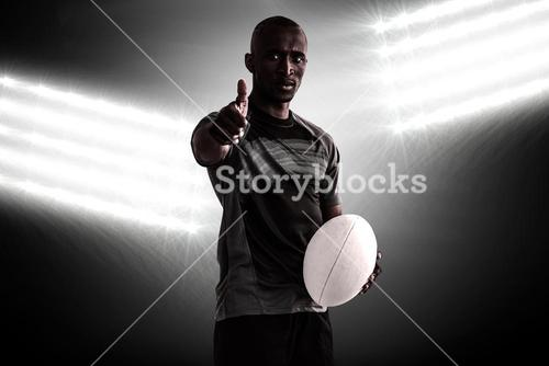 Composite image of portrait of confident rugby player showing thumbs up while standing