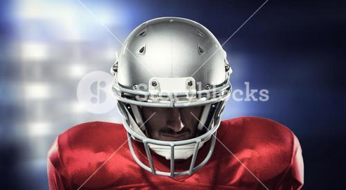 Composite image of close-up of serious american football player in red jersey looking down