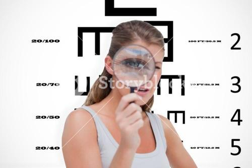 Composite image of young woman looking through a magnifying glass