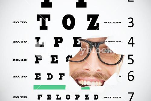 Composite image of geeky hipster looking at camera through hole