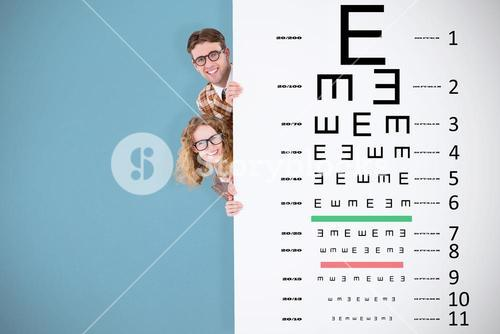 Composite image of geeky hipster holding poster and smiling at camera