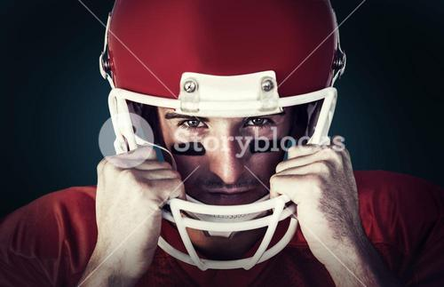 Composite image of portrait of rugby player wit hands on helmet