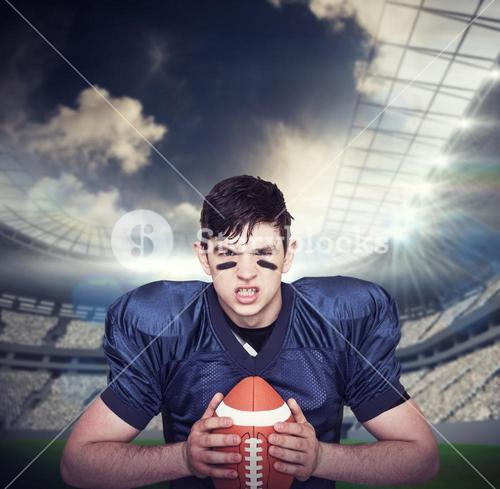 Composite image of enraged american football player holding a ball