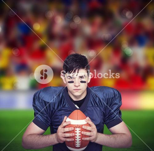 Composite image of determined american football player holding a ball