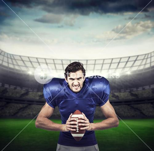 Composite image of aggressive american football player holding ball