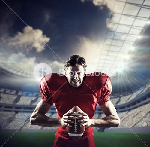 Composite image of aggressive american football player in red jersey holding ball