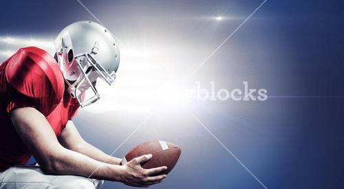 Composite image of american football player crouching while holding ball