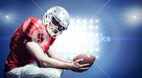 Composite image of portrait of american football player crouching while holding ball
