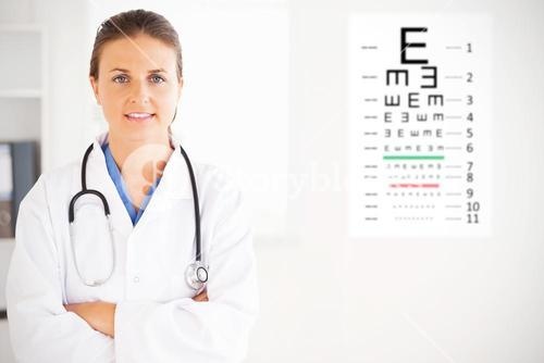 Composite image of charming doctor having a stethoscope around her neck looking into the camera