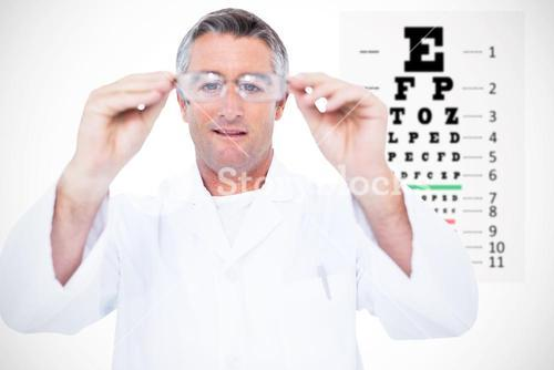 Composite image of optician in coat holding glasses
