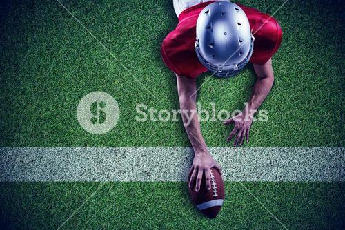 Composite image of american football player lying in front with ball