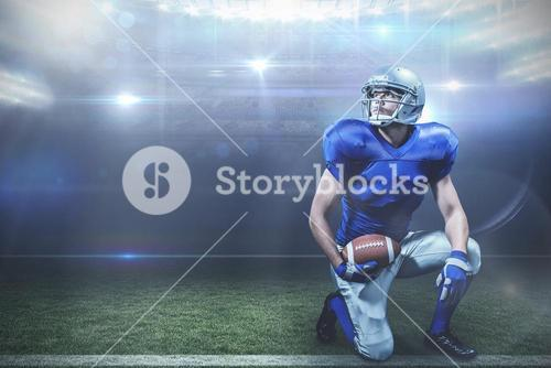 Composite image of american football player with ball kneeling