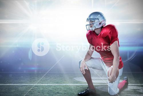 Composite image of american football player looking away while kneeling