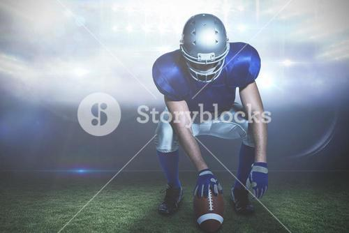 Composite image of american football player holding ball while crouching