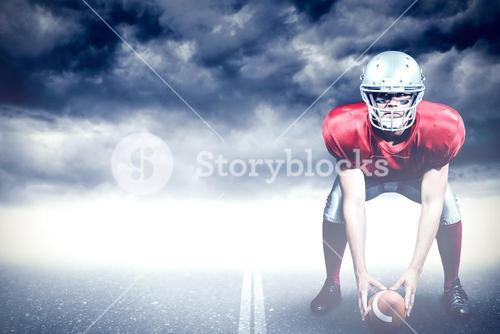 Composite image of american football player bending while holding ball