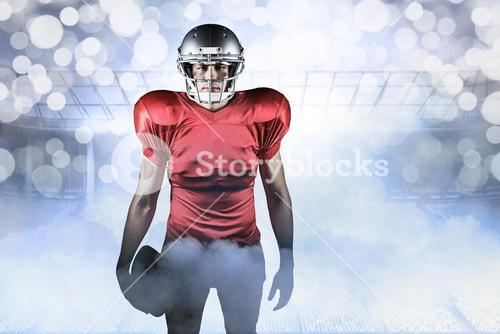 Composite image of portrait of american football player holding ball