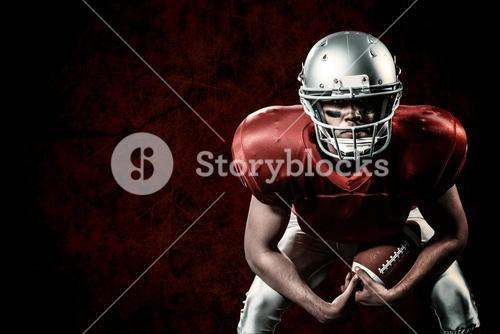 Composite image of portrait of american football player bending while holding ball