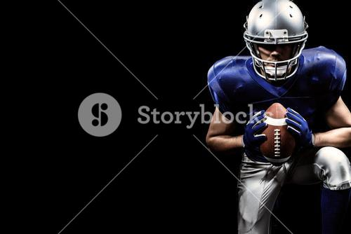 Composite image of determined american football player holding ball while kneeling