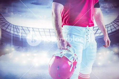 Composite image of american football player holding his helmet