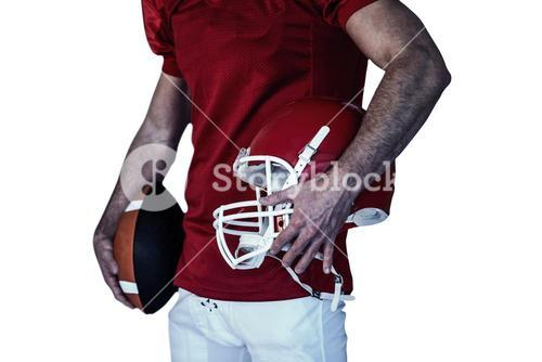 Midsection of player holding rugby ball and helmet