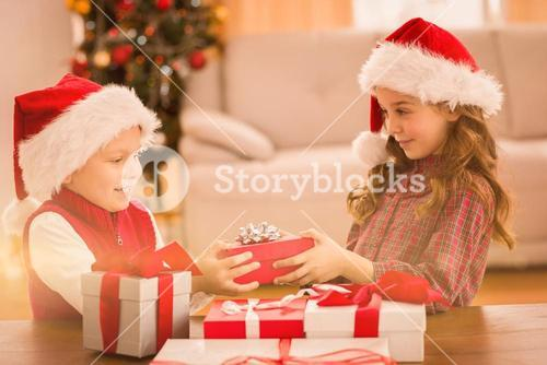 Festive siblings smiling at their gifts