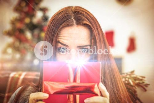 Festive redhead with gift on the couch