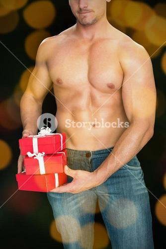 Composite image of muscular man holding pile of presents in blue jeans