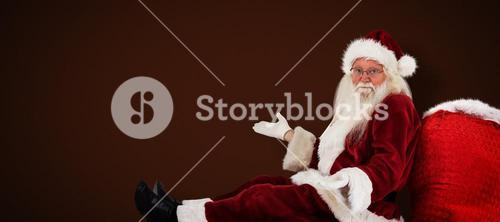 Composite image of santa sits leaned on his bag and has no clue