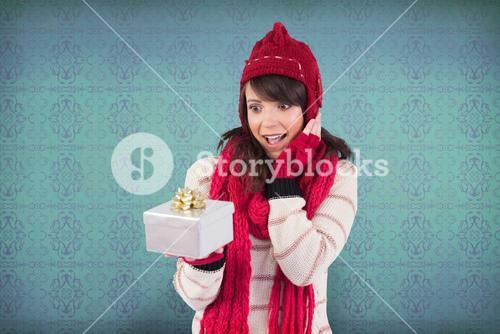 Composite image of surprised young woman holding a wrapped gift