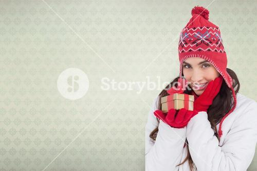 Composite image of surprised brunette in winter clothes holding gift
